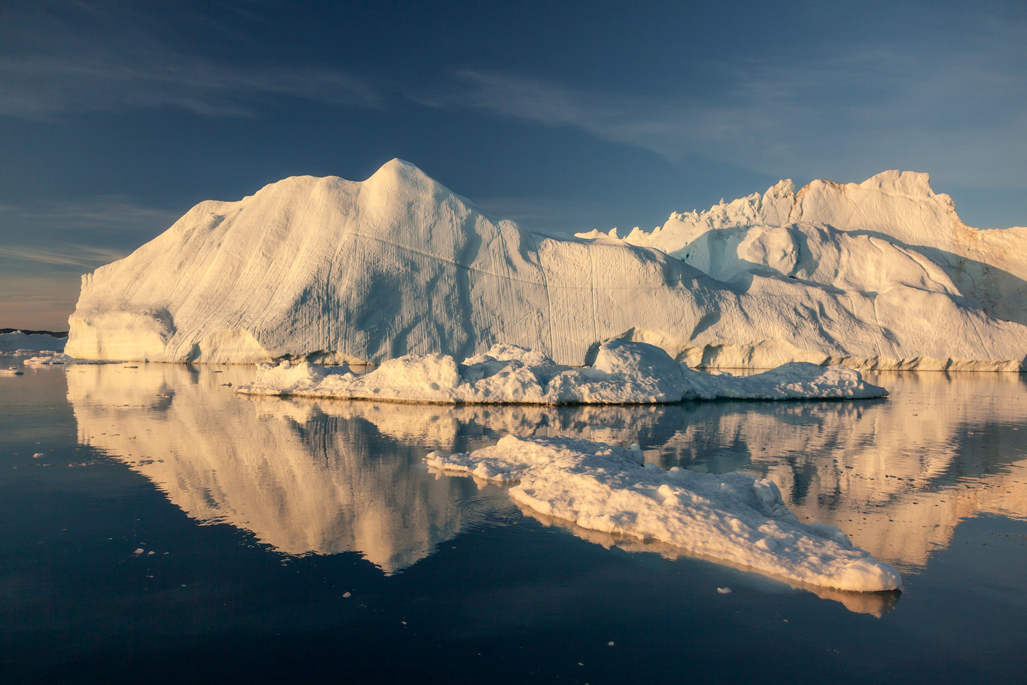 Calm water sets off massive icebergs on the magnificent    Ilulissat Icefjord    near the town of    Ilulissat    in    Greenland   .
