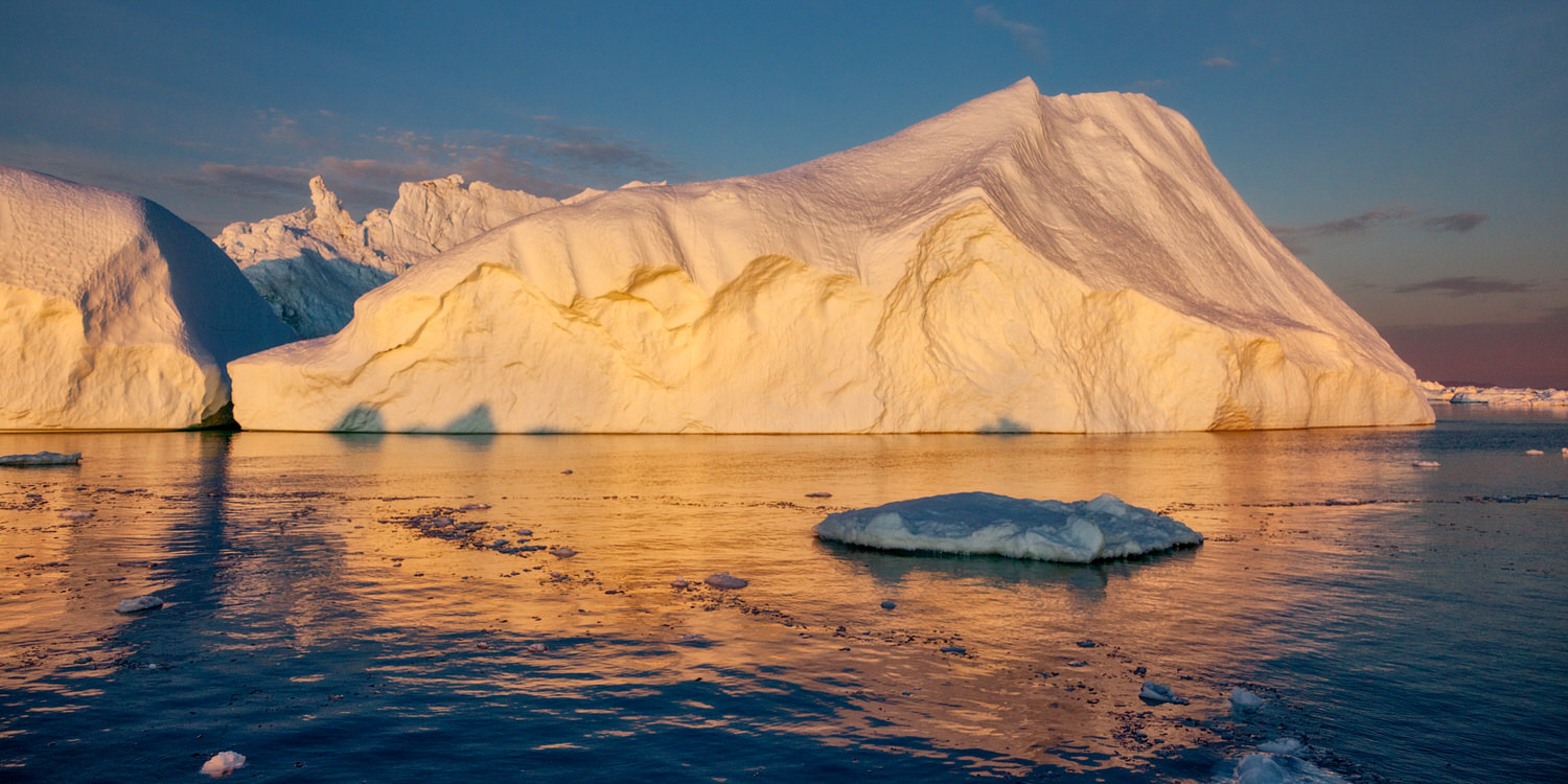 Icebergs    illuminated by the    midnight sun    on the Ilulissat Icefjord near the town of    Ilulissat, Greenland   .
