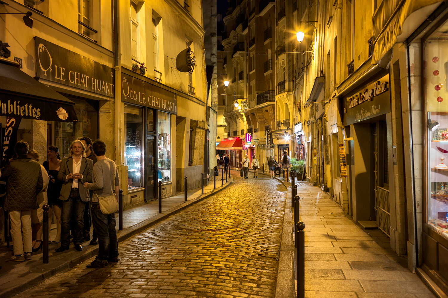 Local Parisians chatting outside a cafe,    Latin Quarter    of Paris at night.