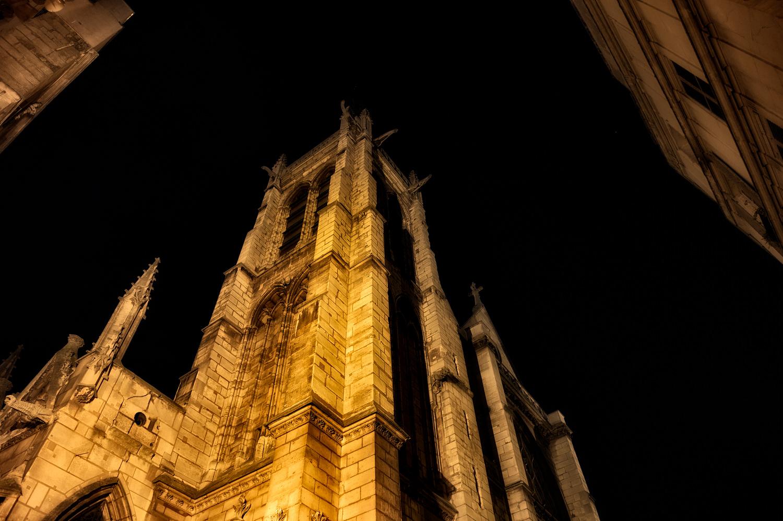 A Latin Quarter Paris church lit with warm, artificial light at night.