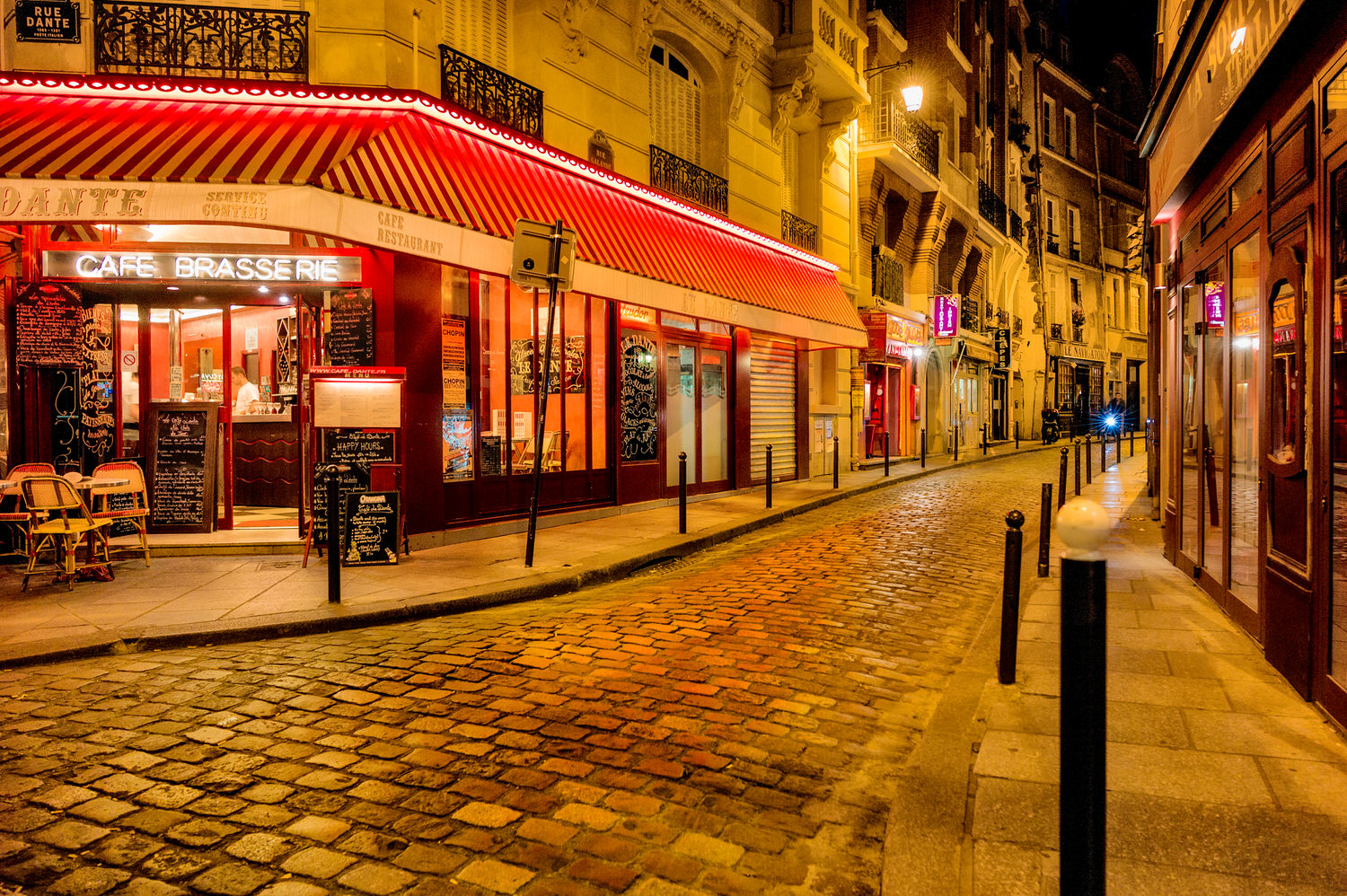 Warm, incandescent street lighting    illuminates the narrow cobbled street outside the    Le Dante Cafe Brasserie    in the Latin Quarter of Paris at night.