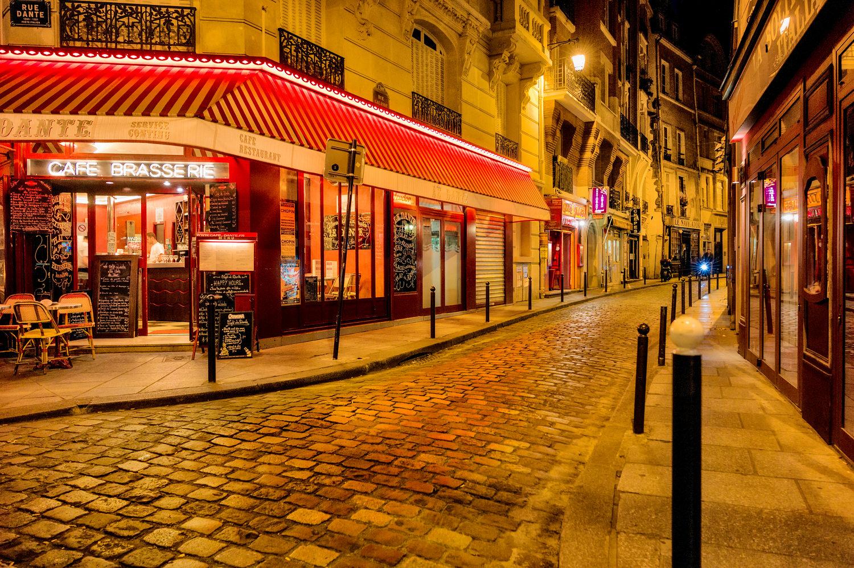 Lighting illuminates cobbled streets in the    Latin Quarter    of    Paris at night  .