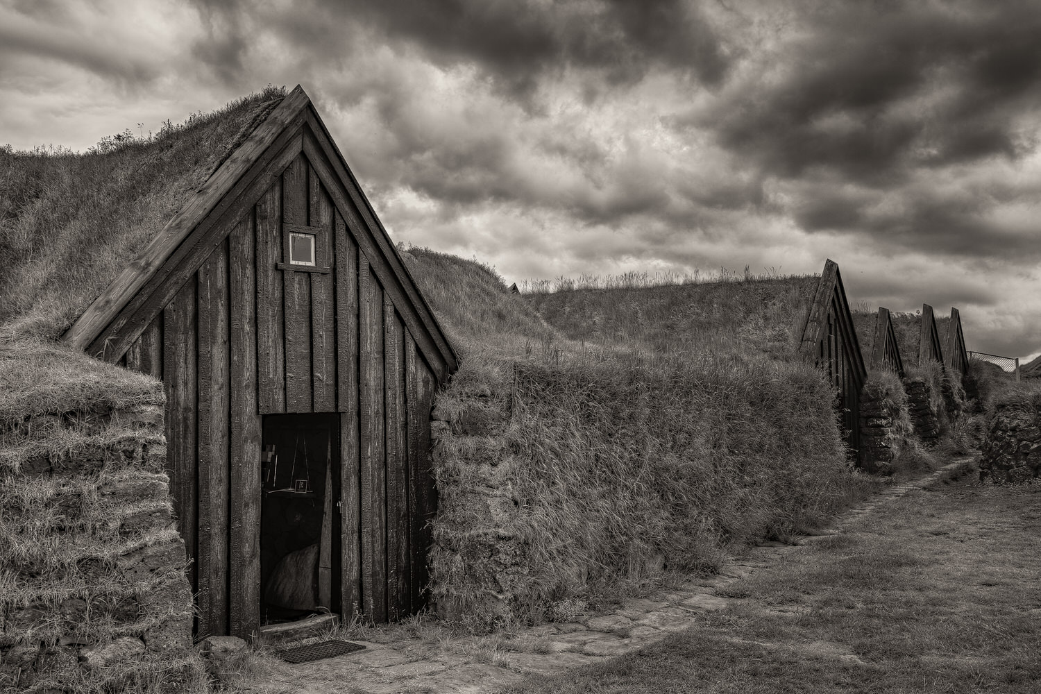 A series of well preserved, grass topped    traditional farm buildings    in southern    Iceland   . The light was silver grey and the approaching storm helped abstract the scene from the now and transport it back in time.