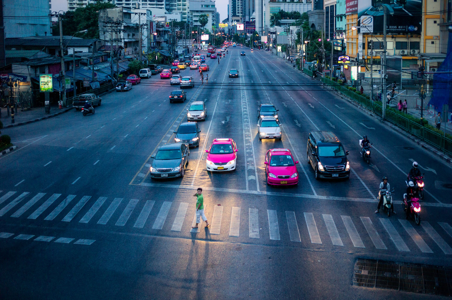 A man casually making his way across a  pedestrian crossing  at dusk in  Bangkok, Thailand .