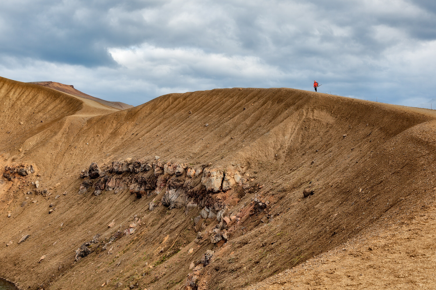 Photographer hiking around the edge of the    Stora-Viti crater    near the town of Myvatn in    Iceland   .