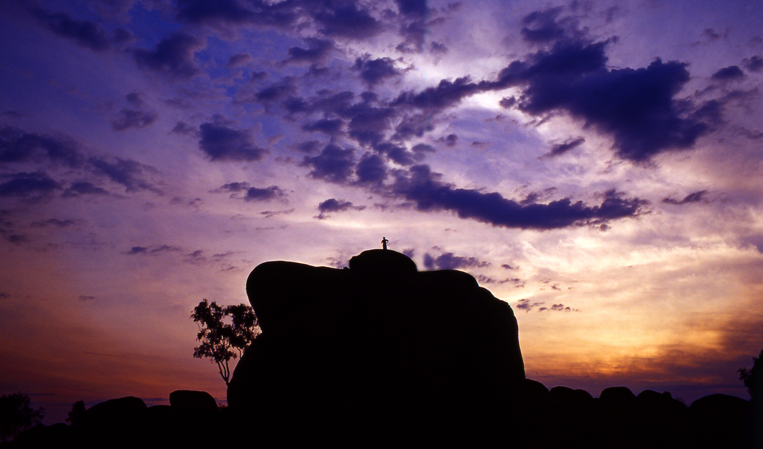 A tiny human figure, on top of a huge bolder backlit by a wonderous sunset, at  Devils Marbles  near the town of  Wycliffe Well  in the  Northern Territory , Australia.
