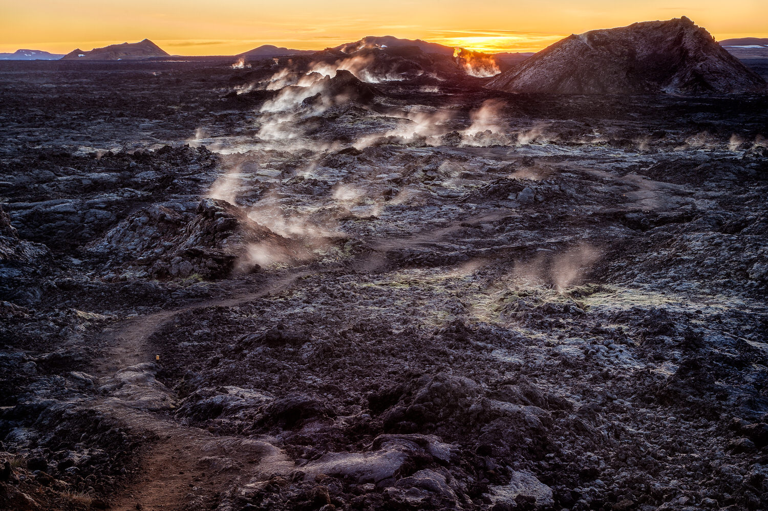A narrow path leads through black ash, that will melt your shoes, and steaming vents in the    Leirhnjukur Lava Fields    near    Myvatn    in    Northern Iceland   .