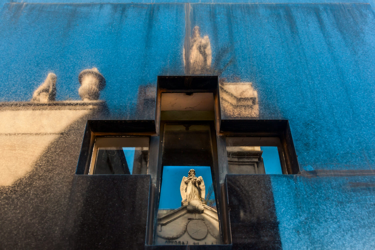 A dynamic view of a    statue reflected    within and above a    crucifix    at the magnificent    La Recoleta Cemetery    in    Buenos Aires, Argentina   .
