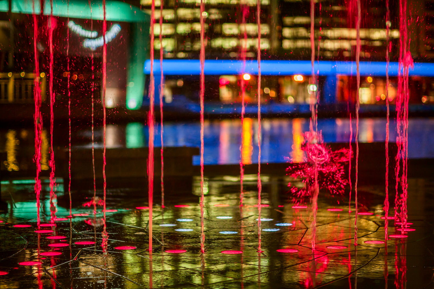 Spirts of water , illiminated at night, spring from the ground at a  fountain  on the boulevard that runs along  Southbank, Melbourne .