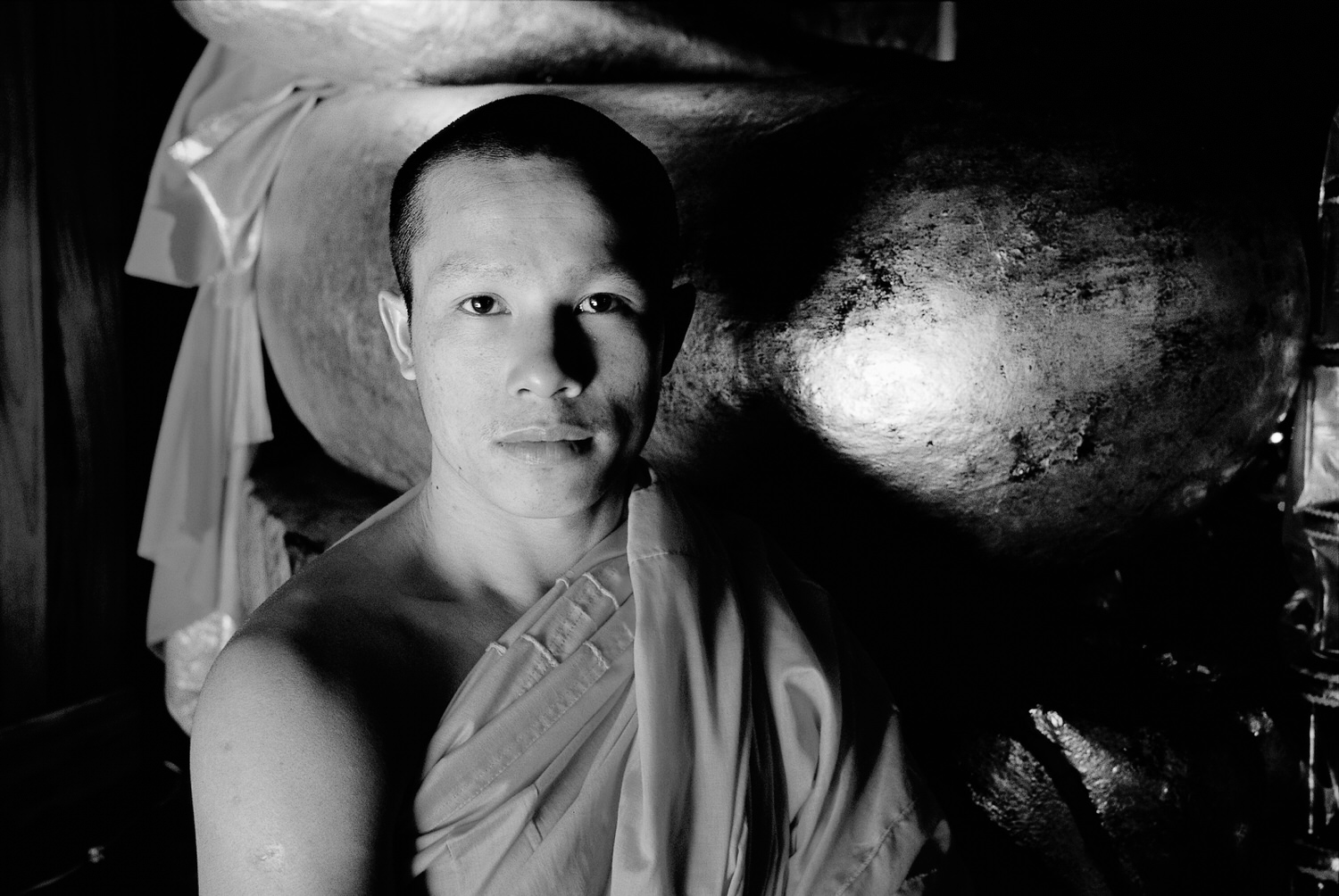 A black and white    portrait of a monk   , made with side light, in a    Buddhist temple    in    Luang Prabang, Laos   .