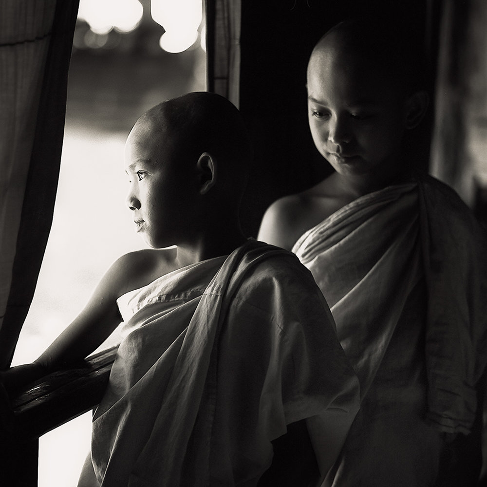 Two young novice monks , lit by side light , standing on a verandah in a monastry in Myanmar .