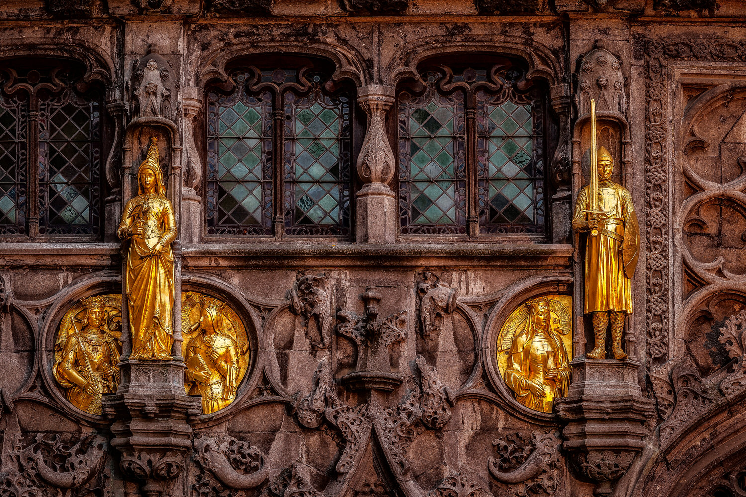 Gold colored figures    decorate the facade of this building in    Bruges, Belgium   .
