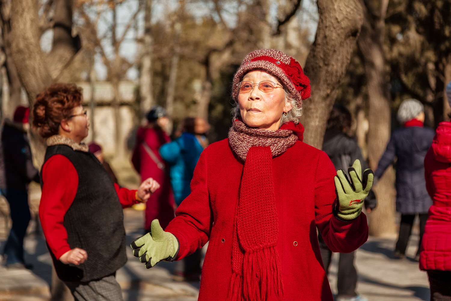 A group of    elderly women dancing    in the grounds of the    Temple Of Heaven   , on a winter's day, in    Beijing, China   . Selective Focus separates the primary subject from the other woman in this photo.