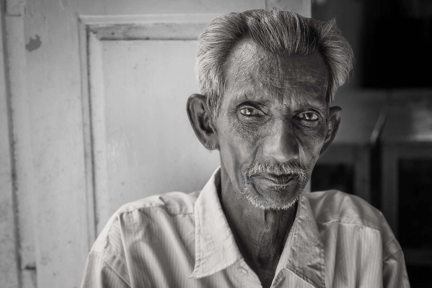 A beautiful black and white portrait of an  elderly man , made with  side lighting , sitting by an open doorway on the outskirts of  Chennai, India .