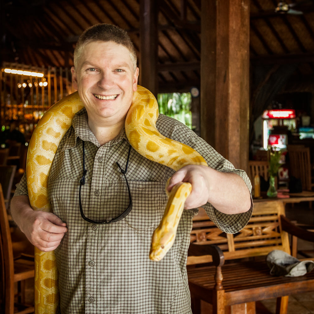 Glenn Guy   , photographer and owner of the Travel Photography Guru website and blog, holding a    python    at    Bali Zoo    in Bali, Indonesia.