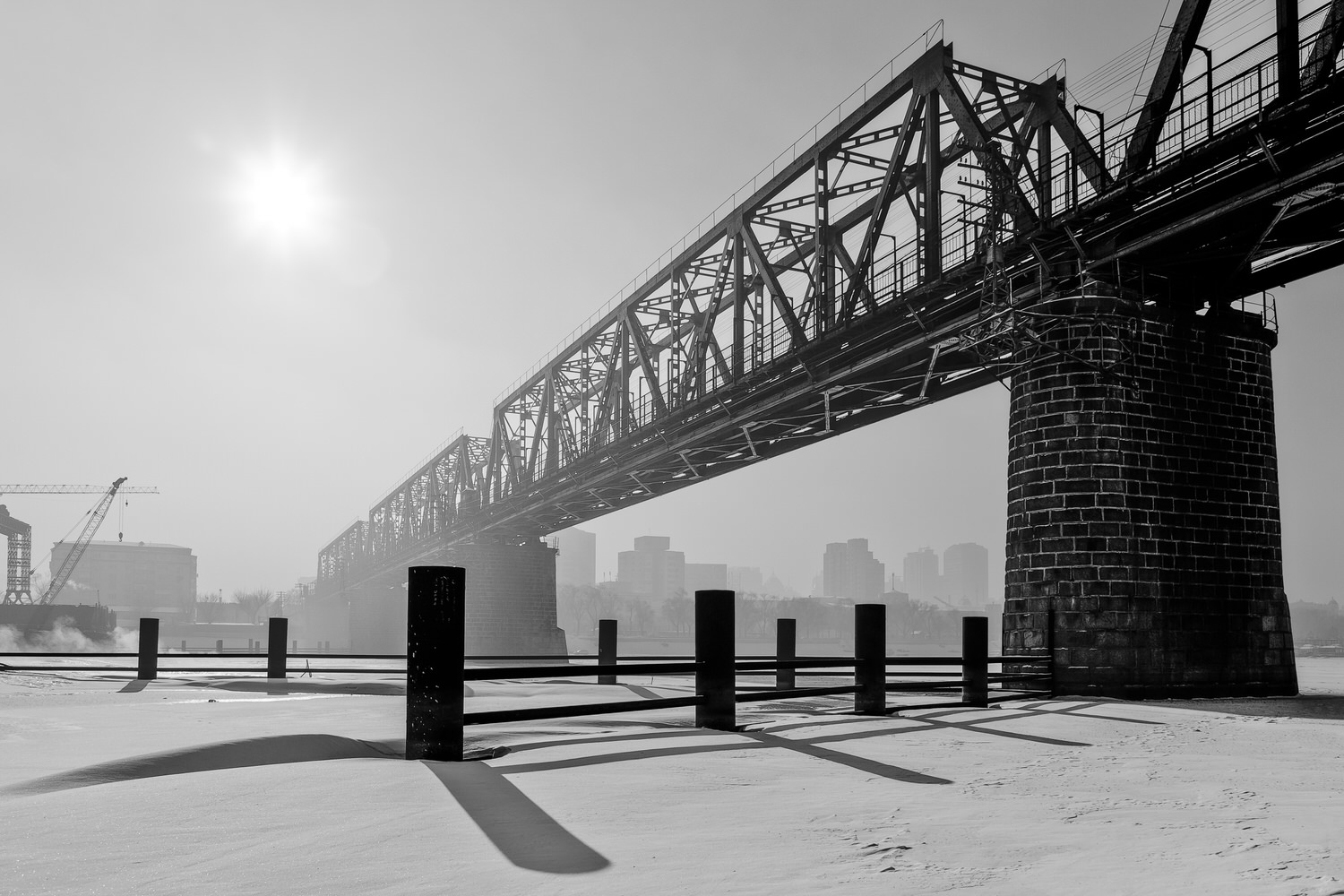 A rail bridge, photographed against intense backlighting, on an overcast winter's day in    Harbin, China   . The strong graphic shapes and shadows make for a dramatic image.