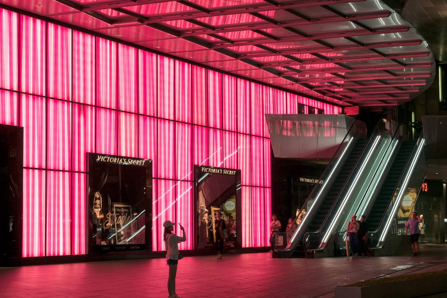 Vibrant    pink light    provides wonderful backlighting for this street scene along the famous    Orchard Road    in    Singapore   .