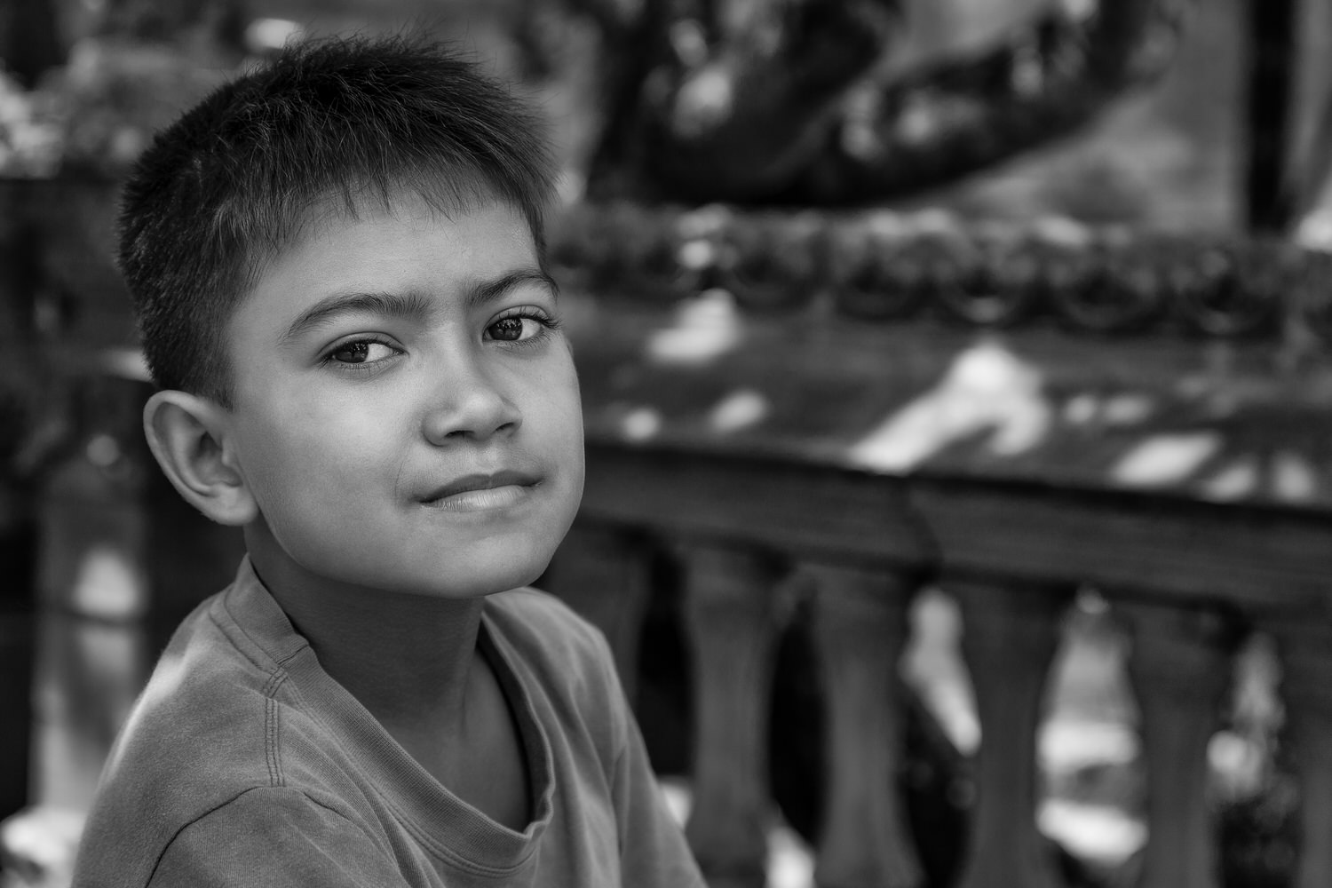 A  black and white portrait  of a  young boy , photographed under open shade, in rural  Bali, Indonesia .