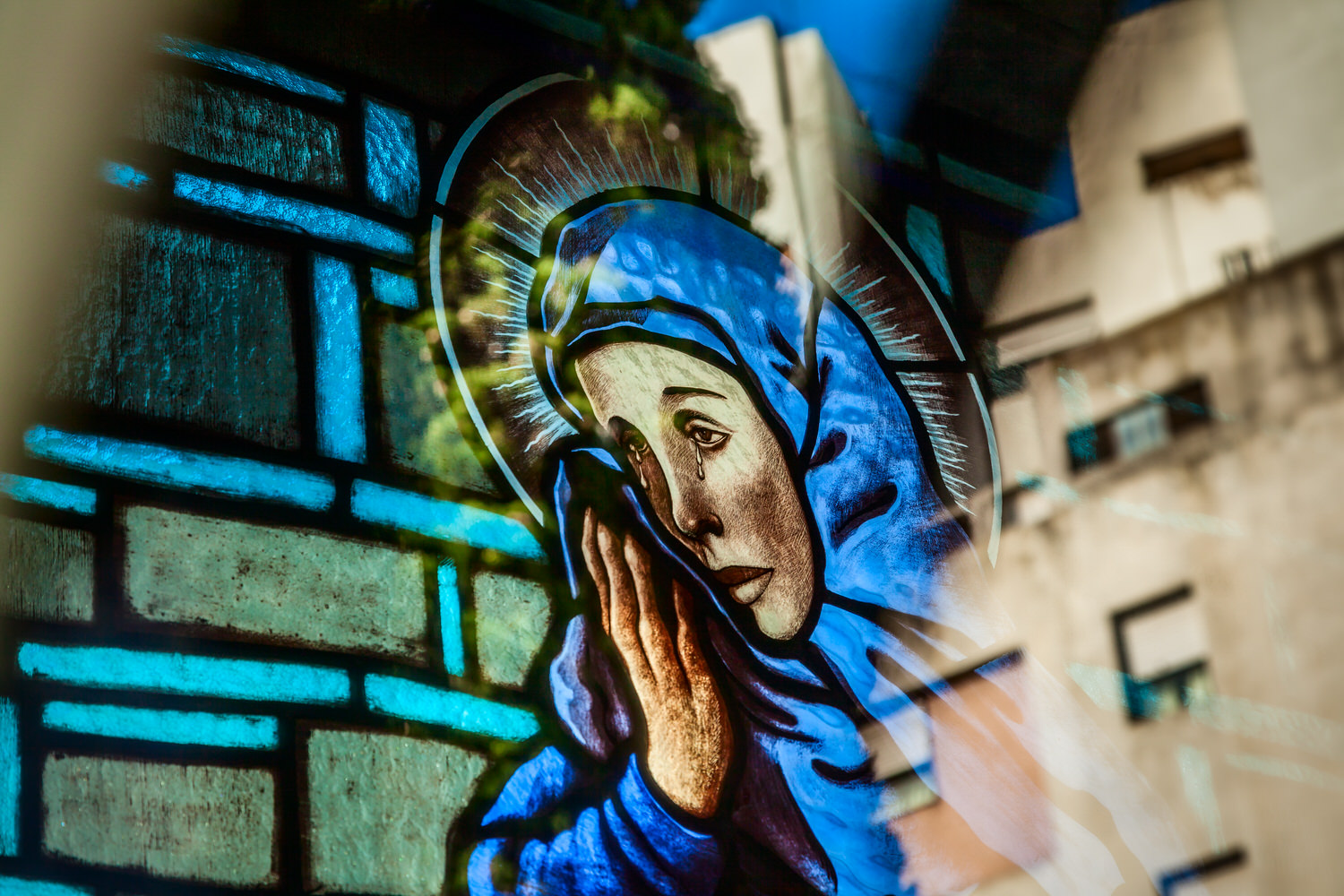 An image of the    Madonna    shedding tears at    La Recoleta Cemetery    in    Buenos Aires, Argentina   . The image hints at the ever encroaching urban sprawl in the background of this beautiful and historic cemetery.