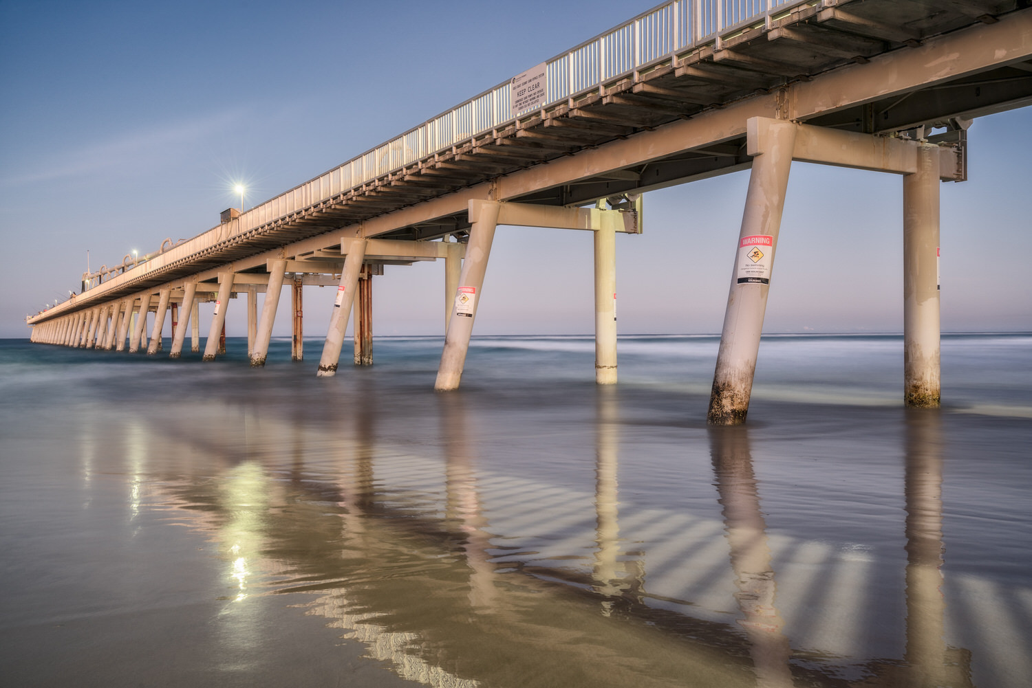 Lights on the  Sand Pumping Jetty  signal the transition from day to night at  The Spit  on Australia's  Gold Coast .