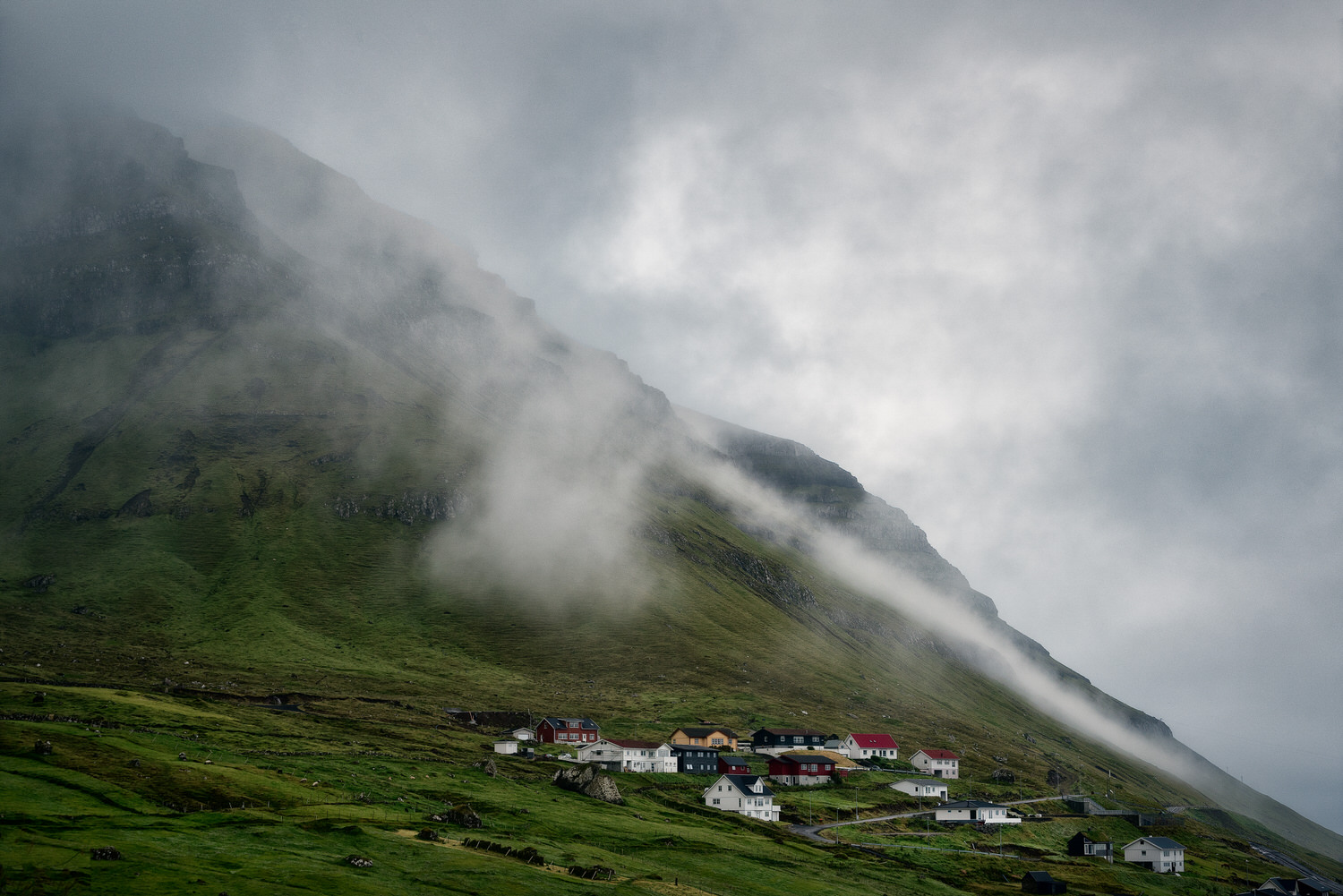 Mist and and rain clouds    hover over the    village of Kunoy    on the island of Kunoy in the    Faroe Islands   .