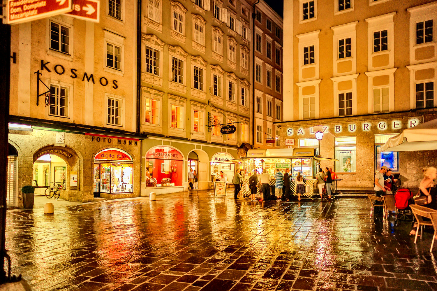 People enjoying a drink amidst a vividly lit street scene in the old town of    Salzburg    on a rainy summer's evening.