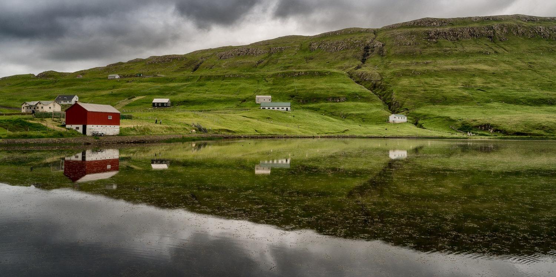 Serene scene of houses around a lake on    Suduroy, Faroe Islands   .