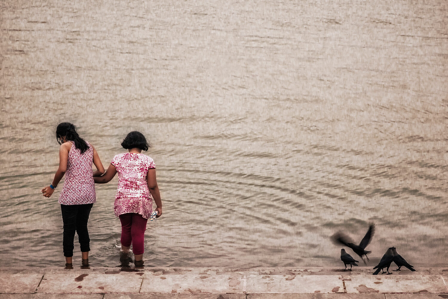 Two girls step anxiously into the waters of the Hooghly River, Kolkata.