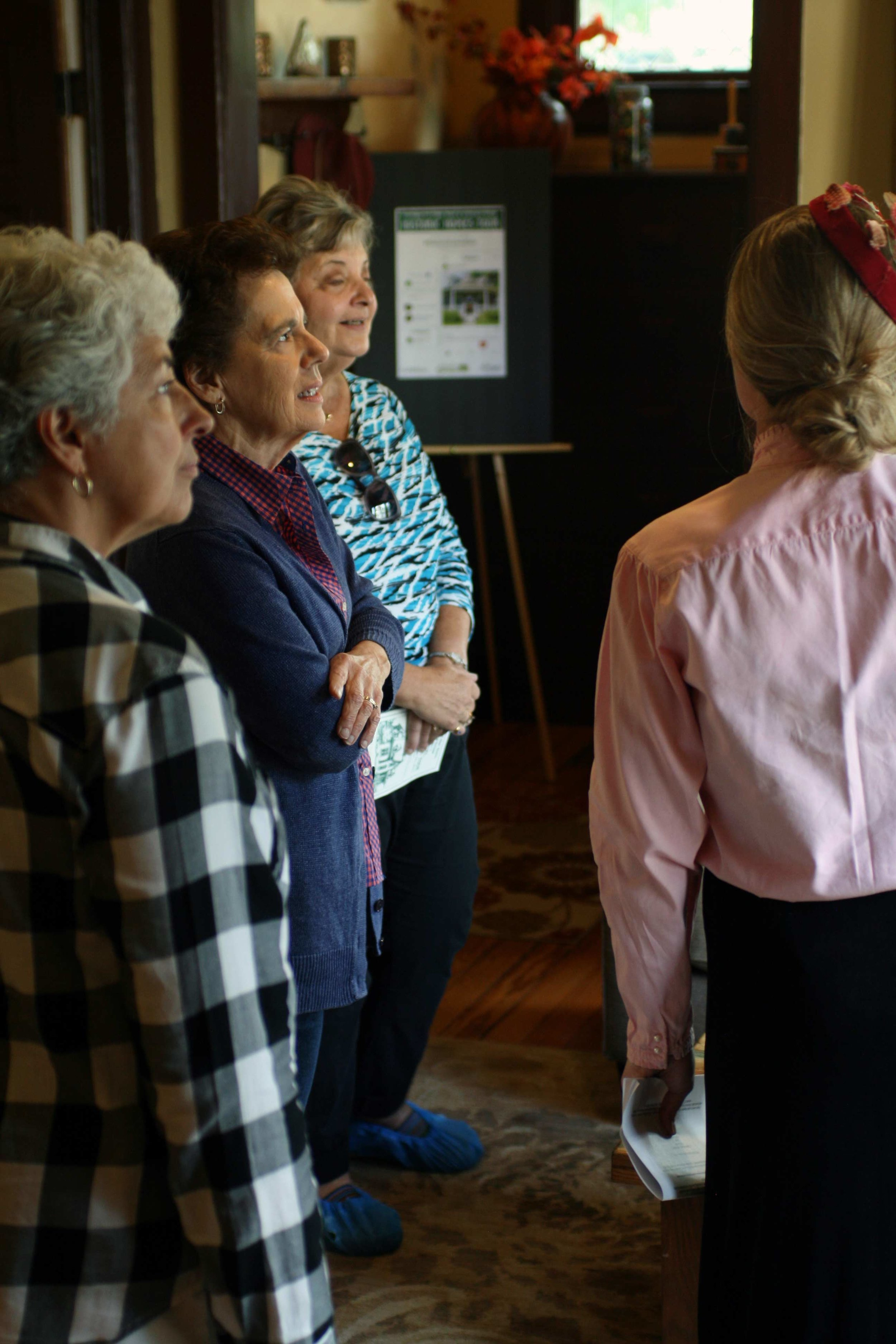 A volunteer docent informs attendees about the antique furniture in a historic home on Smith Street in Fort Collins