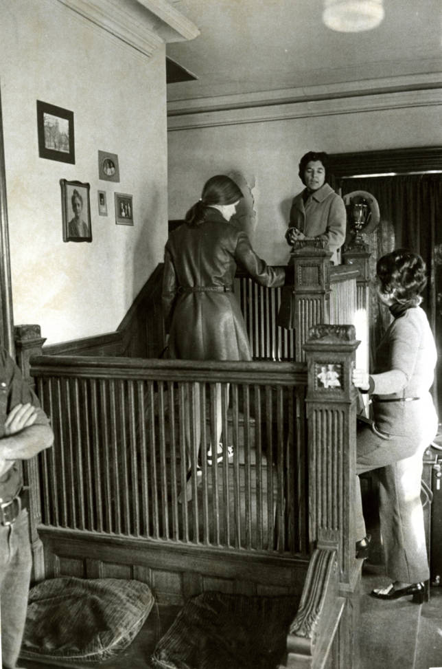 Circa 1960. Black and white photograph of the interior of the Avery House located at 328 West Mountain Avenue; Fort Collins, Colorado. Peggy Reeves, Mable Prible, and June Bennett stand on the stairs in the living room.