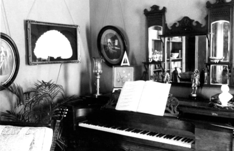 Circa 1980. This photo shows a close view of the piano against the wall in the corner of a room and the decorations on and around it.