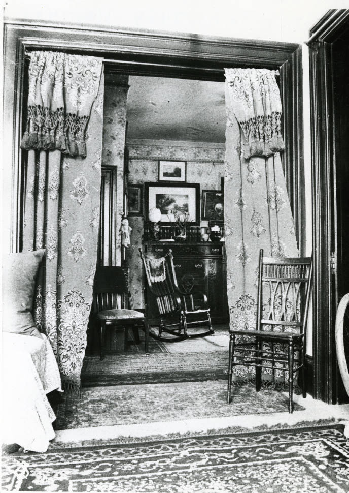 Circa 1900 - Black and white photograph of the interior of the Avery House located at 328 West Mountain Avenue; Fort Collins, Colorado. This is photo is taken from the Parlor looking into the sitting room.