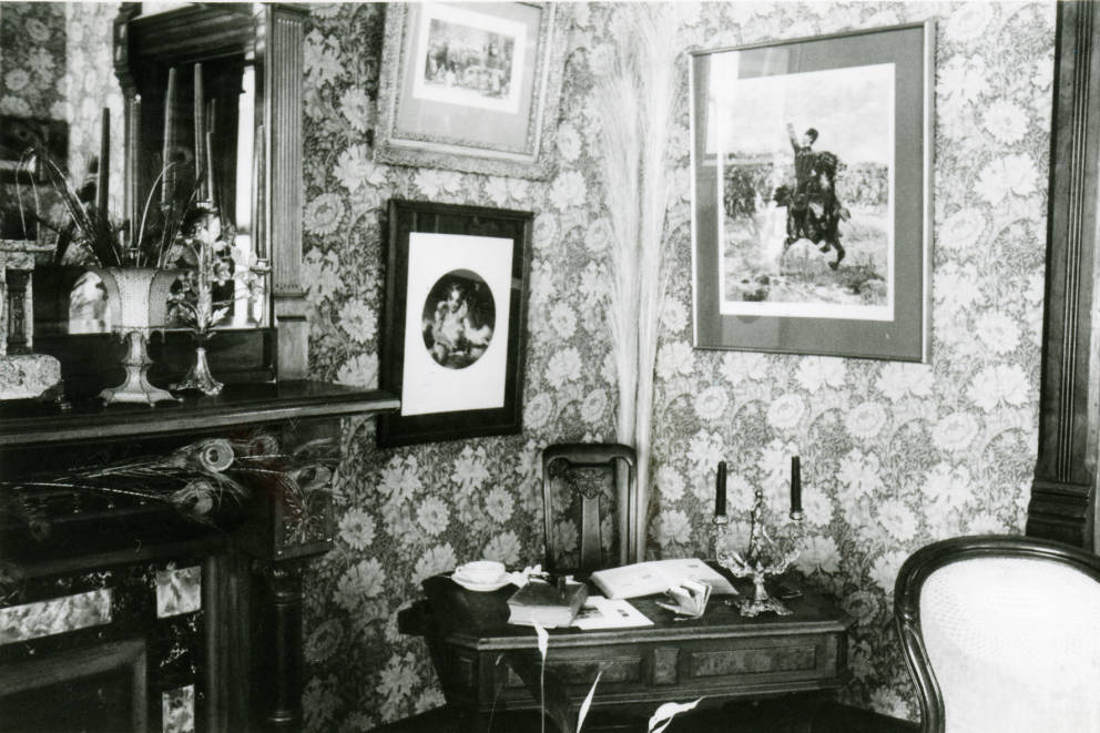Circa 1980 - Black and white photograph of the interior of the Avery House located at 328 West Mountain Avenue; Fort Collins, Colorado. This photo shows the furnishings and decorations of a corner of a room.
