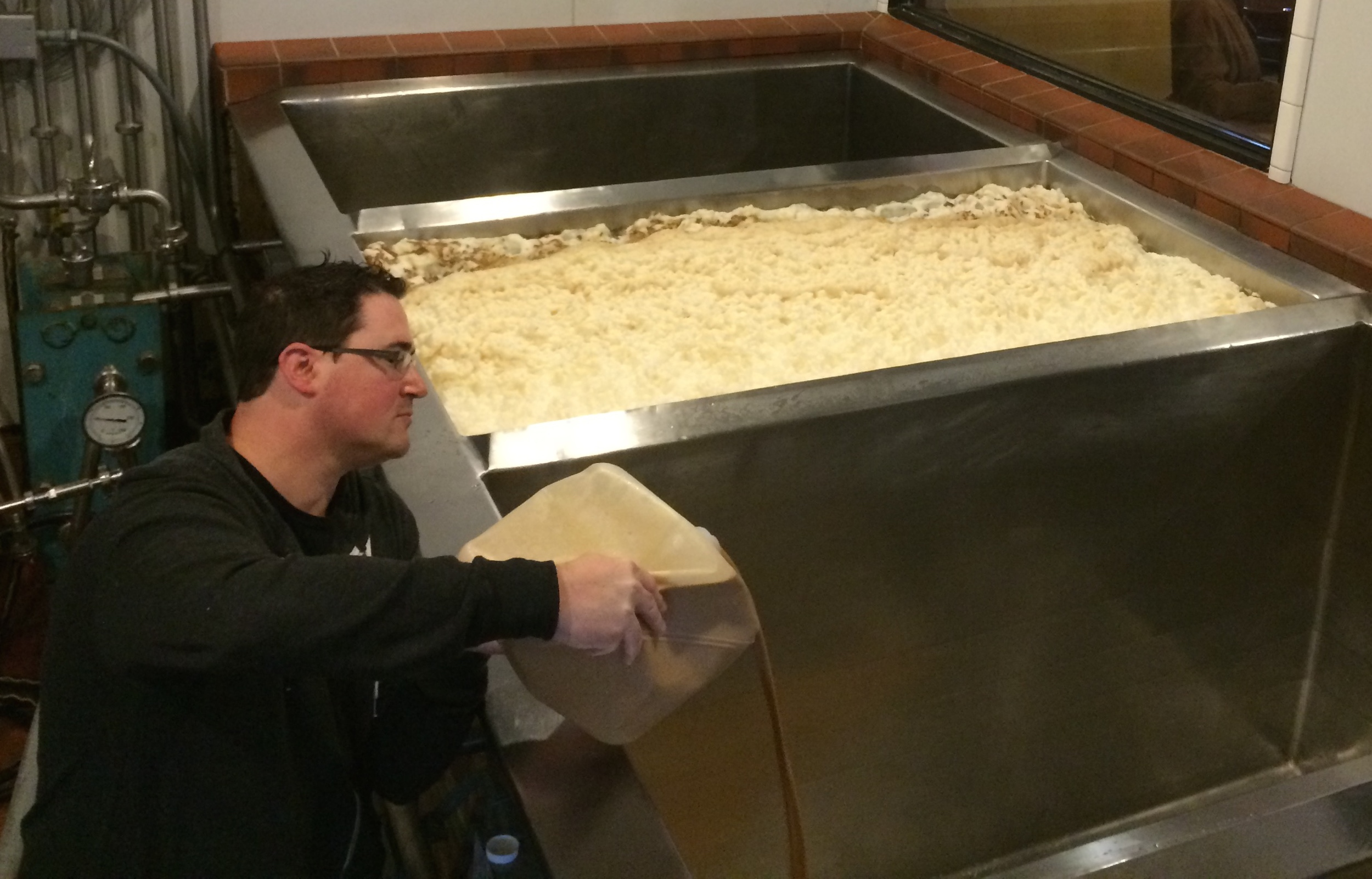 Peter Hoey of BSG CraftBrewing pitches the Saison yeast for the Fünke Canadien into an open-fermentation tank at Sudwerk Brewery in Davis, Calif., in February.