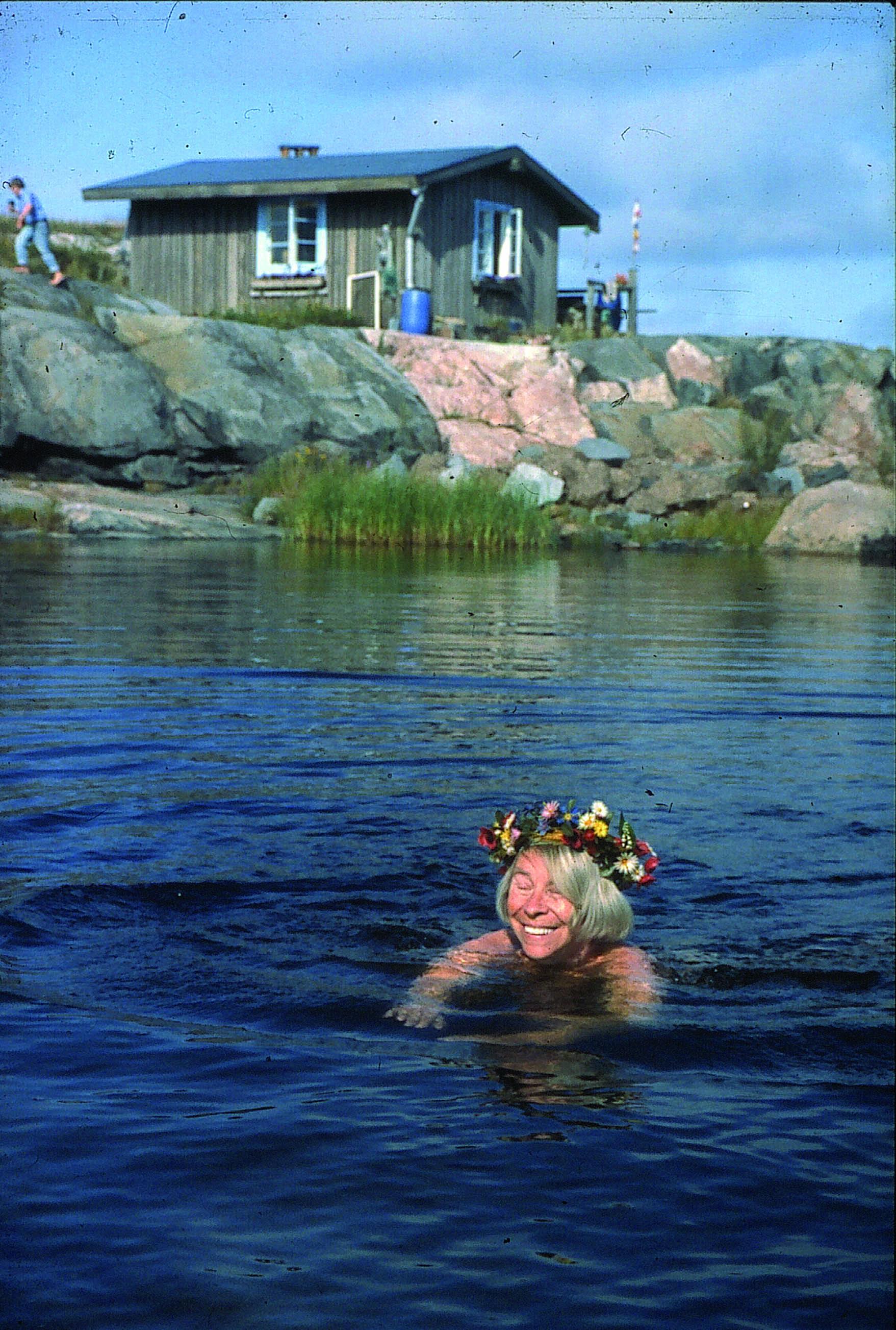 Tove kukkaseppeleuinnillaan. Hänellä oli tapana juhlistaa syntymäpäiväänsä 9.8. uimalla seppele päässä. Kuva: Moomin Characters.
