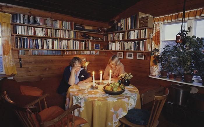 Tooti ja Tove lukevat kynttilän valon ääressä. Mökissä oli ikkunat jokaiseen ilmansuuntaan. Kuva: Per-Olov Jansson, Moomin Characters.
