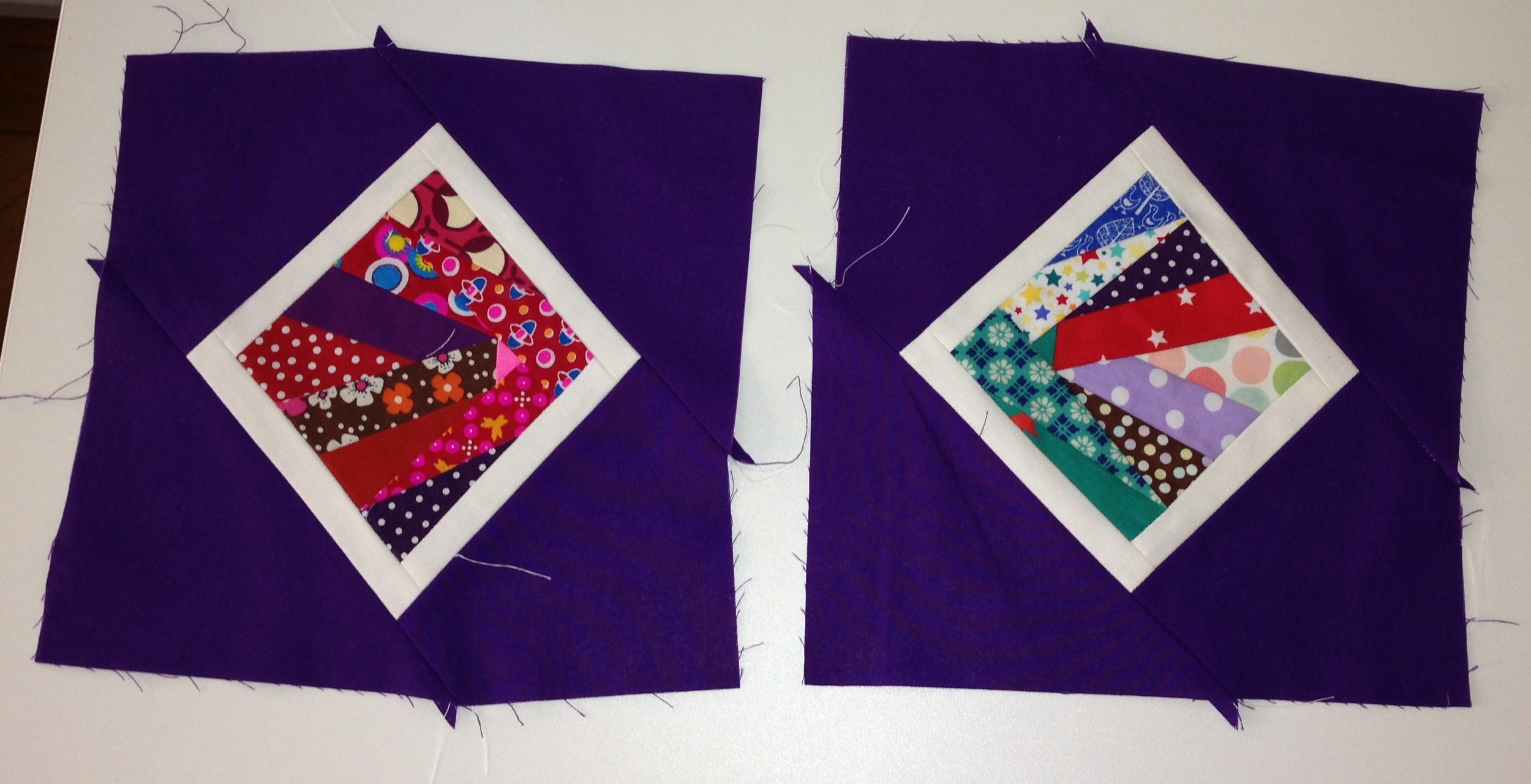 Two of the five p  aper pieced   blocks, framed in white and purple solids (Aug 2013)