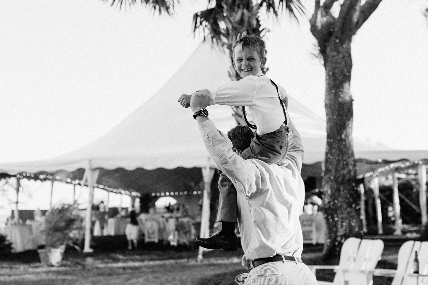 excited kid on dads shoulders wedding reception east coast beach