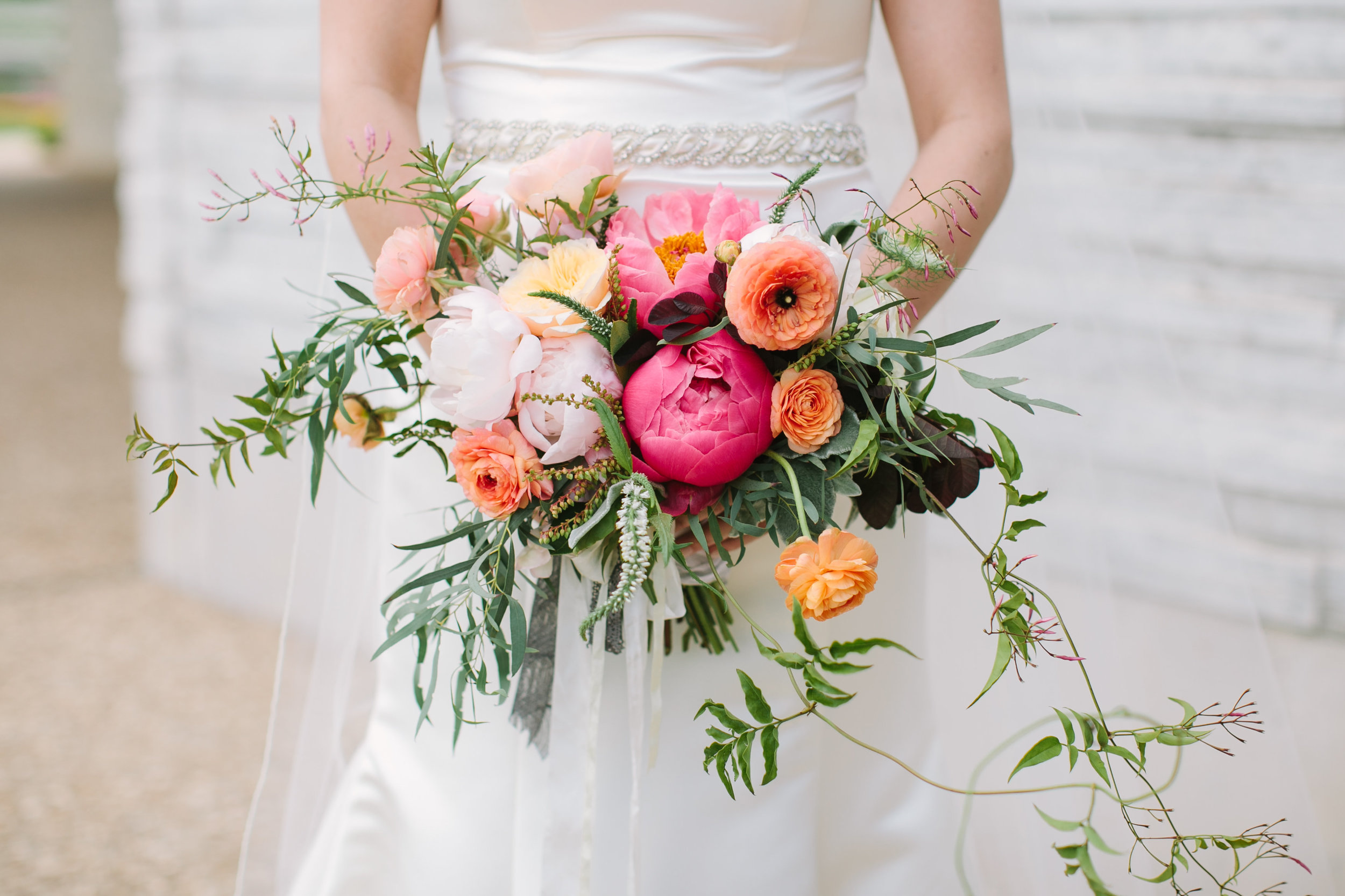 Christi's bouquet included:  Flowering jasmine vine, lambs ear, feather eucalyptus, coral charm and pink peonies, peach ranunculus, lysmachia, pieris japonica buds, juliet david austin garden roses, and smokebush.