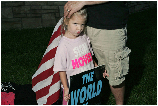 """With a sign reading """"The World is Doomed"""", Faith Drain, 4, joins her father Steve, 43, at a picket of The Laramie Project at Kansas State University. Manhattan, KS. 2008."""