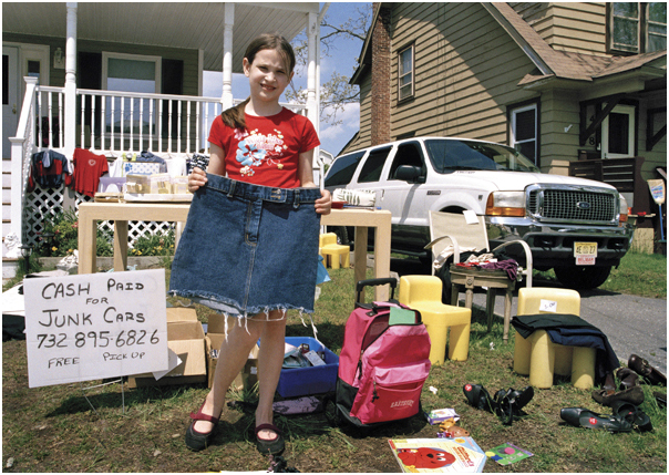 Girl shows denim skirt for sale at her family's garage sale. Belmar, NJ. 2008.