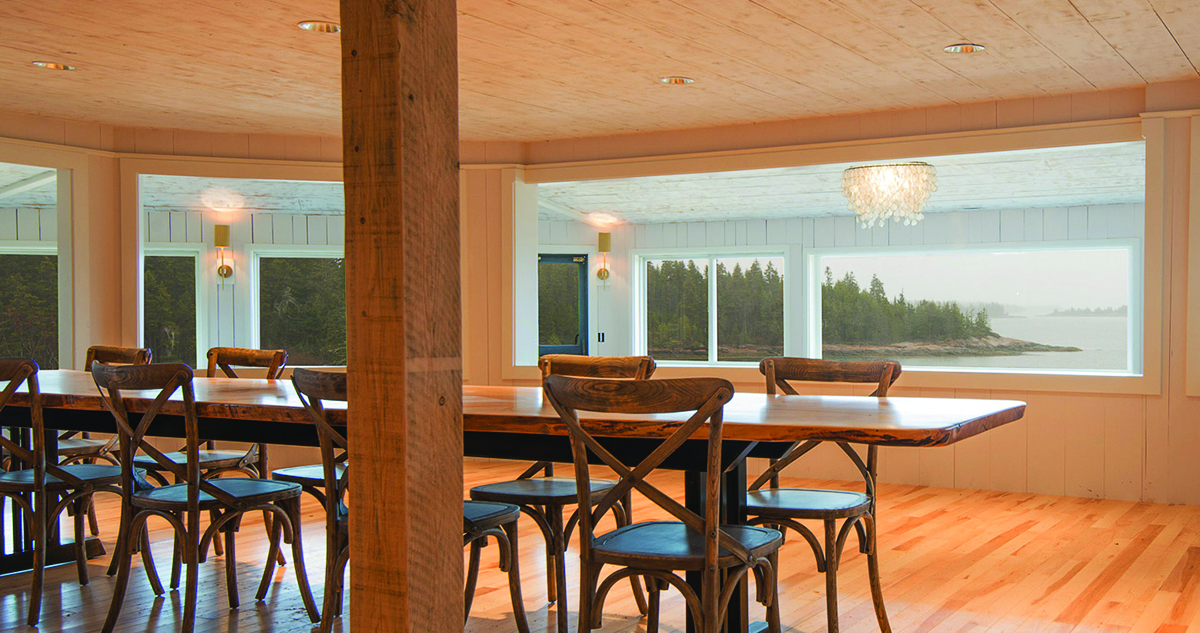 The newly renovated dining room has a light, up to date feel with warm wood floors, clean walls, and views over the deck to the water.   Photo courtesy: Aragosta