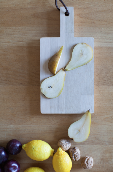 Cut pear on a wood board by  Ledansla