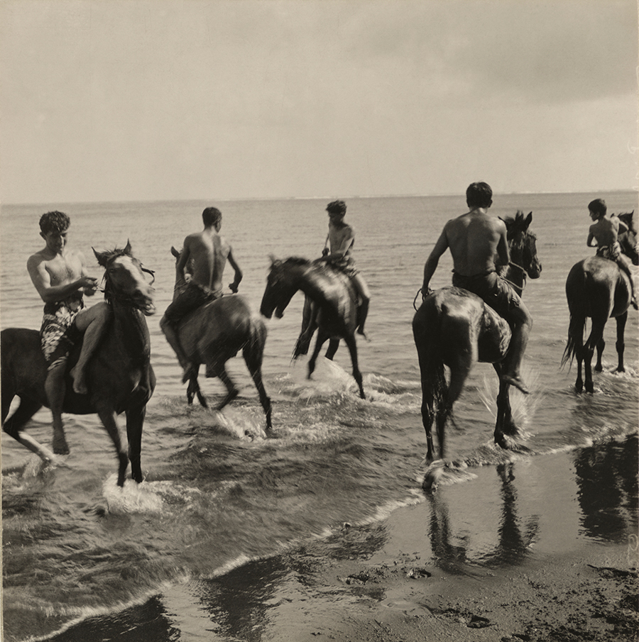 Men on horseback run through the surf in Tahiti, 1922.