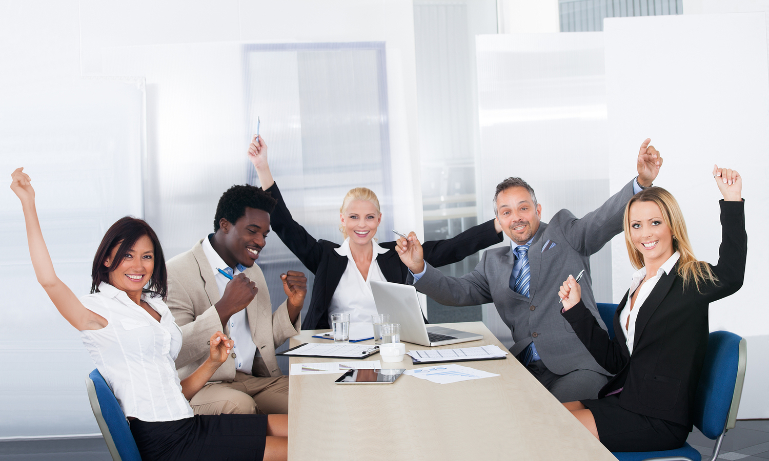 A team of engaged employees sitting at a conference table, celebrating a recent success.