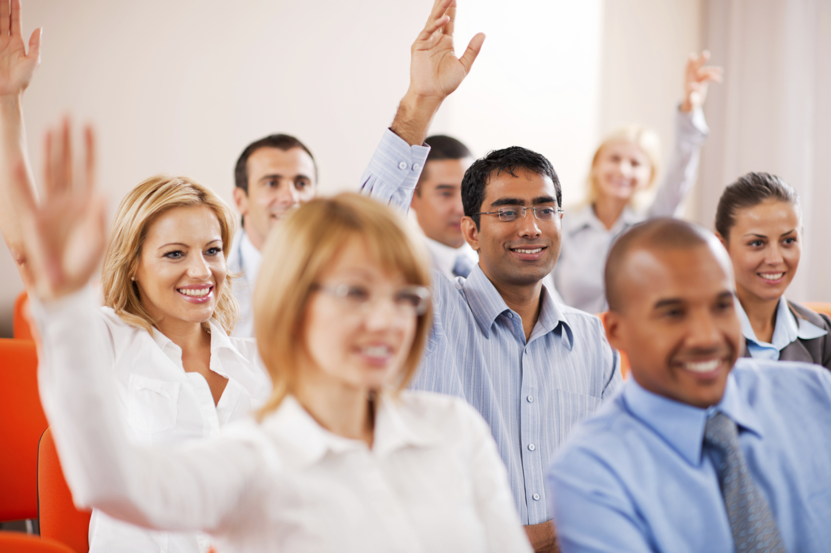 A group of smiling employees are attending a training class and raising their hands to participate.