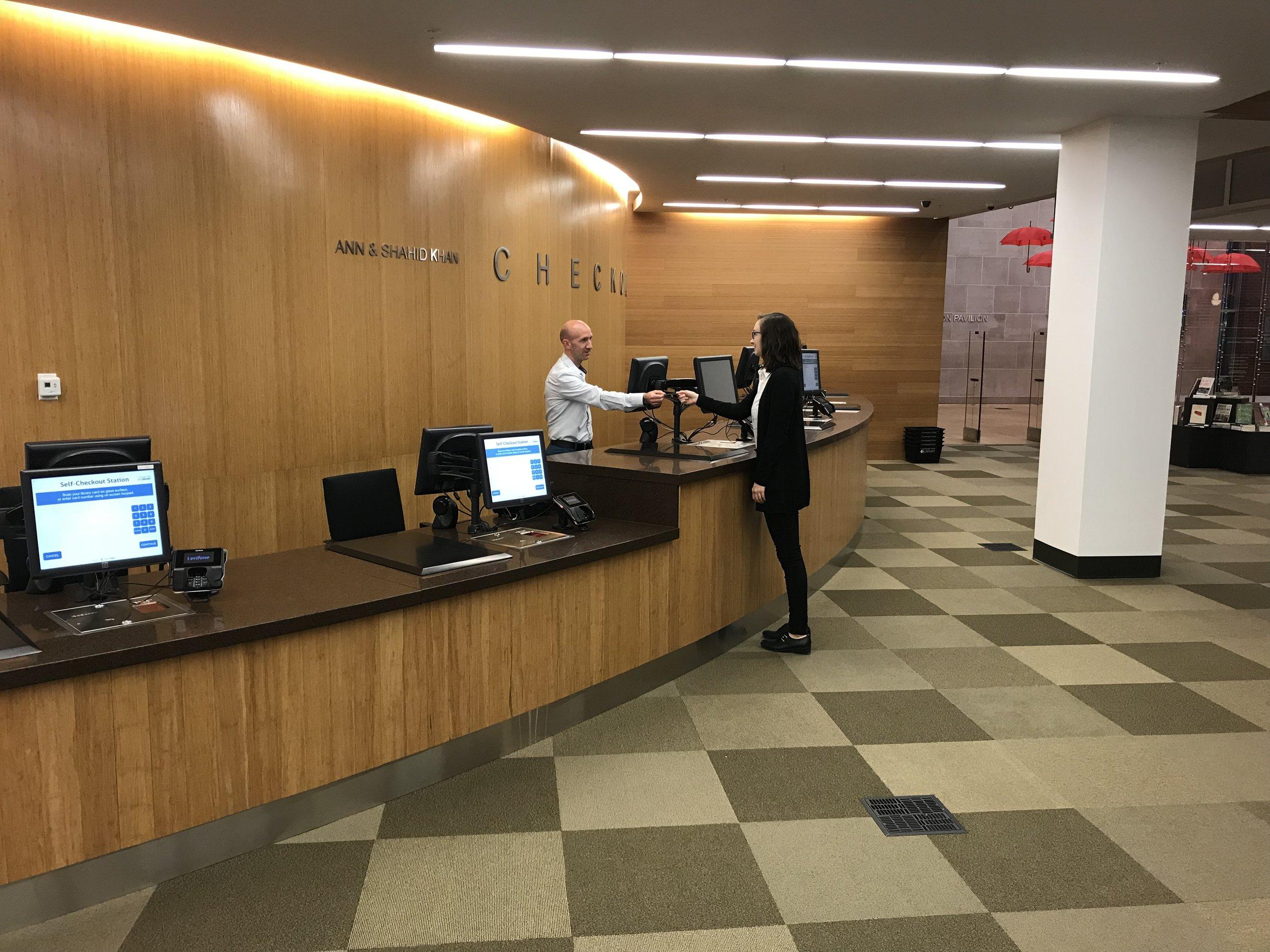 Ruairi McEnroe assists a customer at the Champaign Public Library.