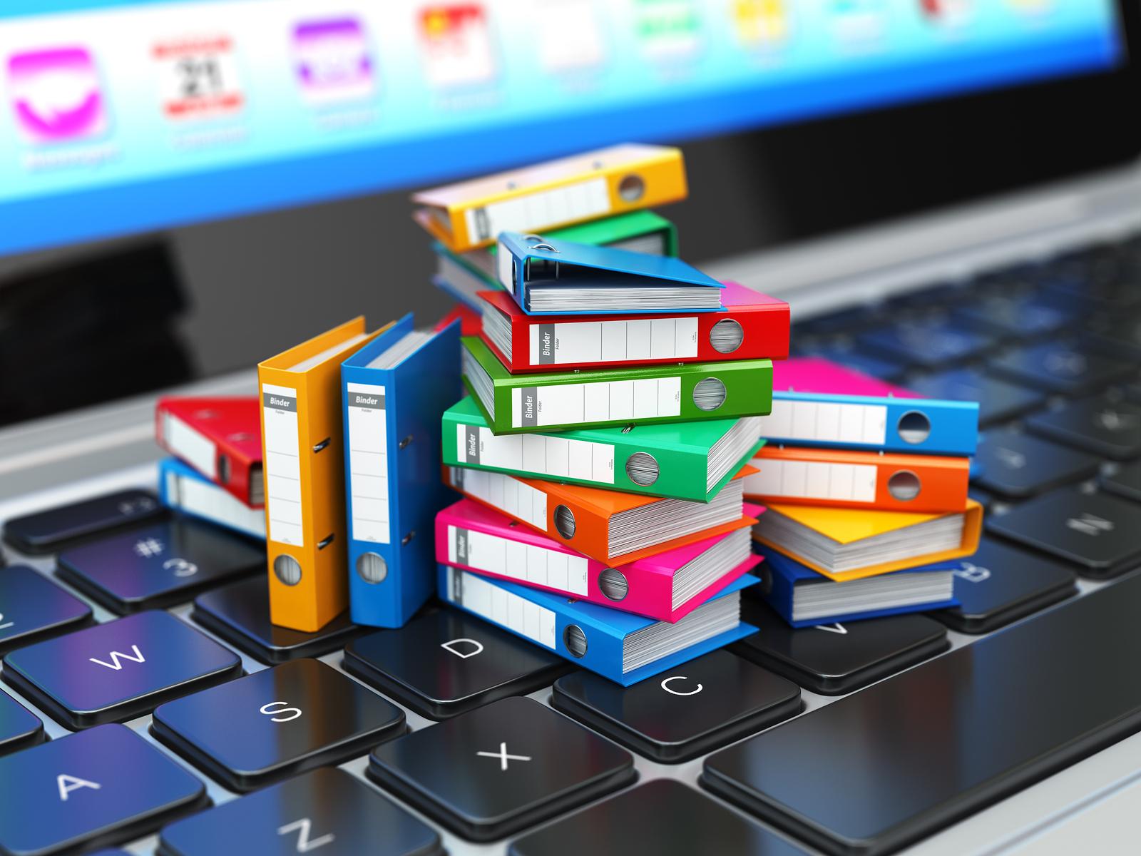 Tiny three-ring binders sitting on a computer keyboard.