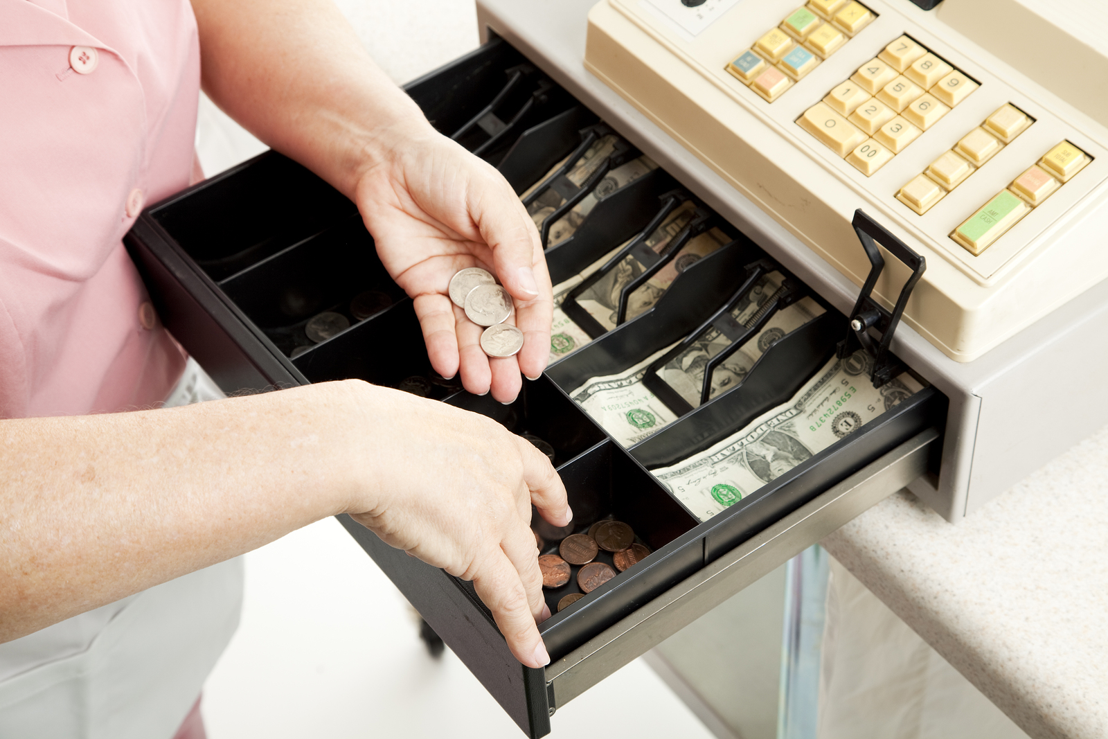 A cashier counting change out of a cash till.