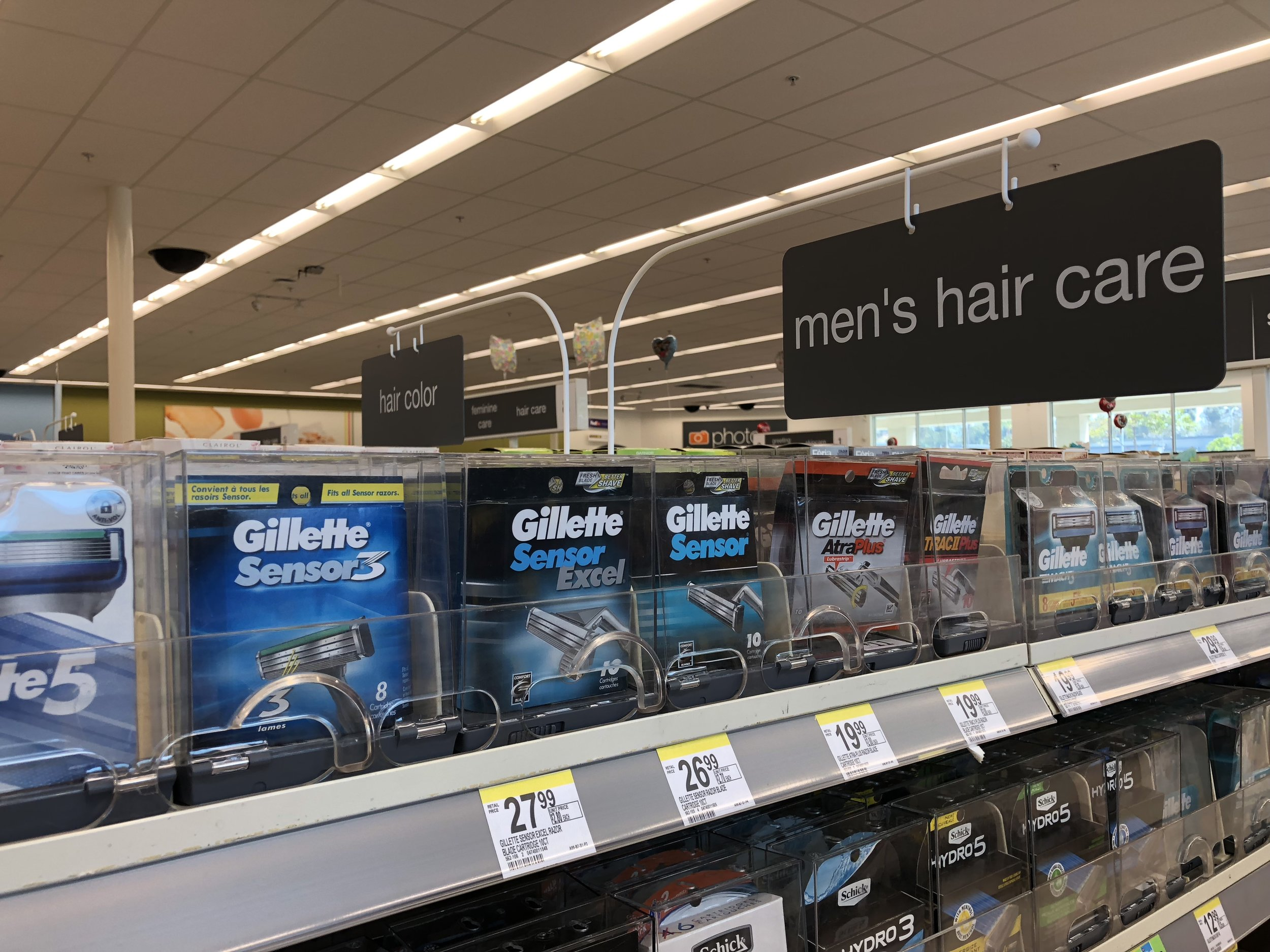 Men's hair care sign hung over the shaving section.
